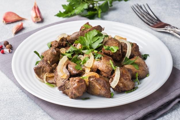 Gebackene hühnerleber mit zwiebel auf einer platte.