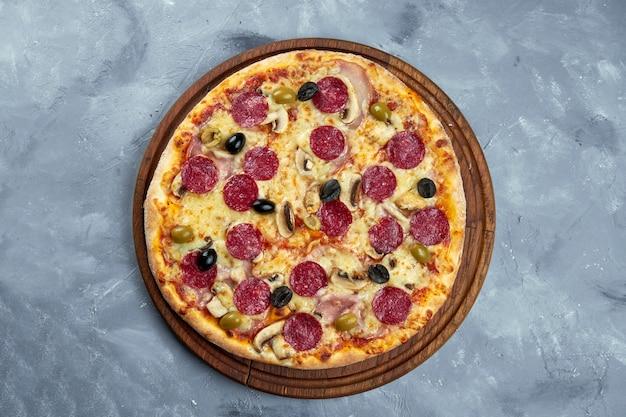 Gebackene italienische pizza mit salami, oliven, pilzen auf einem holztablett auf grauem hintergrund.