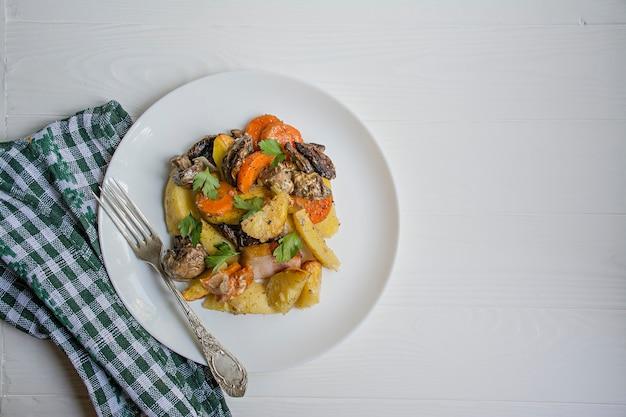 Gebackene junge kartoffeln mit fleisch und gemüse. dunkler hölzerner hintergrund.
