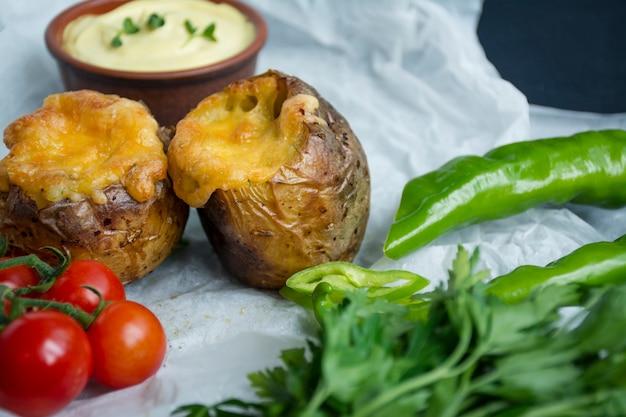 Gebackene junge kartoffeln mit käse. dunkler tisch. nahansicht. platz für text.