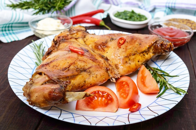 Gebackene kaninchenbeine auf einem teller und verschiedene saucen für fleisch