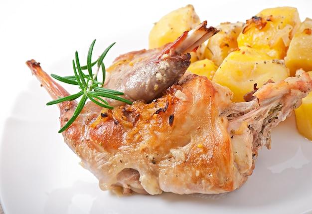 Gebackene kaninchenkeulen mit kartoffeln und rosmarin