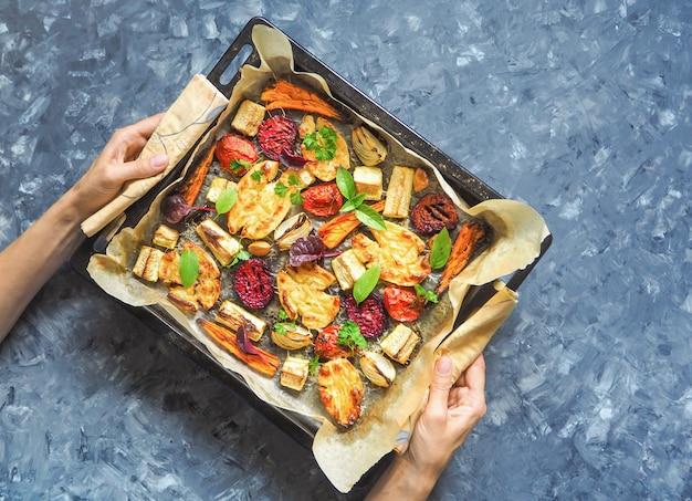 Gebackene karotten, rüben, kartoffeln, zucchini und tomaten auf einem backblech, draufsicht