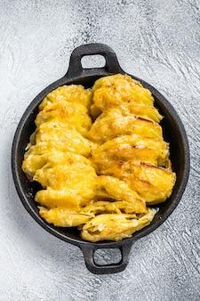 Gebackene kartoffelgratin dauphinois in einer pfanne. draufsicht.
