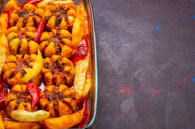 Gebackene kartoffeln aus der nähe von oben mit hackfleisch in form auf dem dunklen hintergrund.