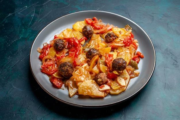 Gebackene kartoffeln der halben draufsicht mit fleischbällchen und gemüse innerhalb platte auf dunkelblauem hintergrund.