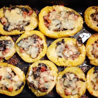 Gebackene kartoffeln mit pilzen, fleisch und käse.