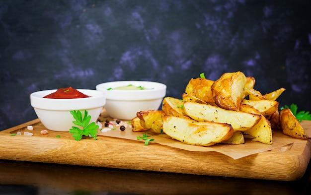Gebackene kartoffeln mit sauce und gewürzen auf dunklem