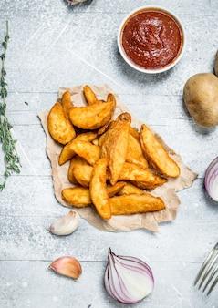 Gebackene kartoffelscheiben mit tomatensauce. auf einem rustikalen tisch.
