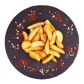 Gebackene kartoffelschnitze auf schwarzem teller