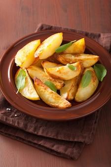 Gebackene kartoffelschnitze im teller über braunem rustikalem tisch