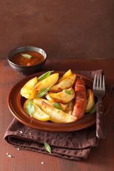 Gebackene kartoffelschnitze und wurst im teller über braunem rustikalem tisch