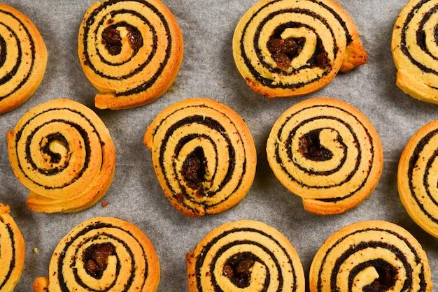 Gebackene kekse mit rosinen und mohn auf einer spur.