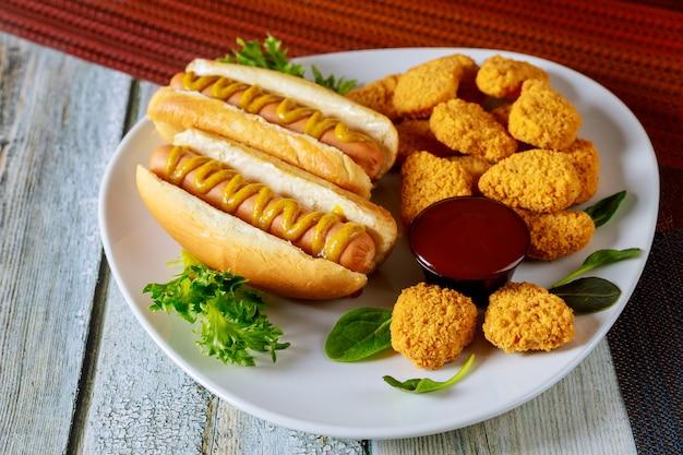 Gebackene knusprige hühnernuggets und hot dogs auf weißem teller.