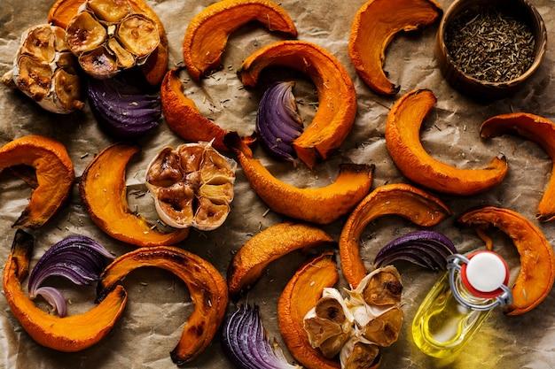 Gebackene kürbisscheiben, zwiebeln, knoblauch, gewürze und käsescheiben dorblu auf pergamentpapier und altem blauen stein