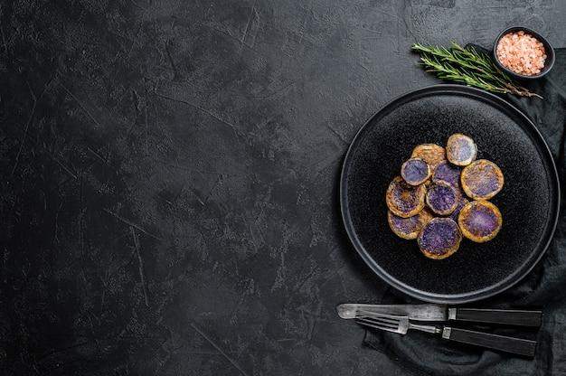 Gebackene lila kartoffeln mit rosmarin. ansicht von oben.