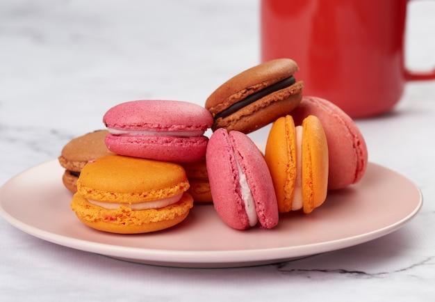 Gebackene macarons auf einem rosa teller, hinter einer roten keramikschale mit kaffee