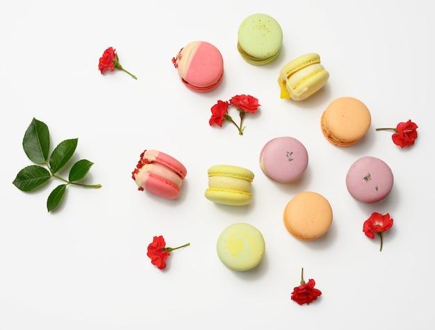 Gebackene macarons mit verschiedenen geschmacksrichtungen und rosenknospen auf weißem hintergrund, ansicht von oben