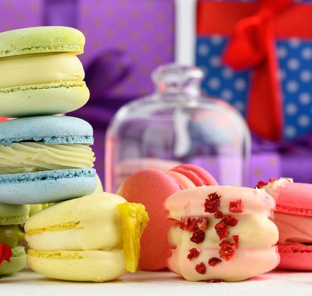 Gebackene macarons mit verschiedenen geschmacksrichtungen und rosenknospen auf weißem hintergrund, hinter geschenkboxen, nahaufnahme