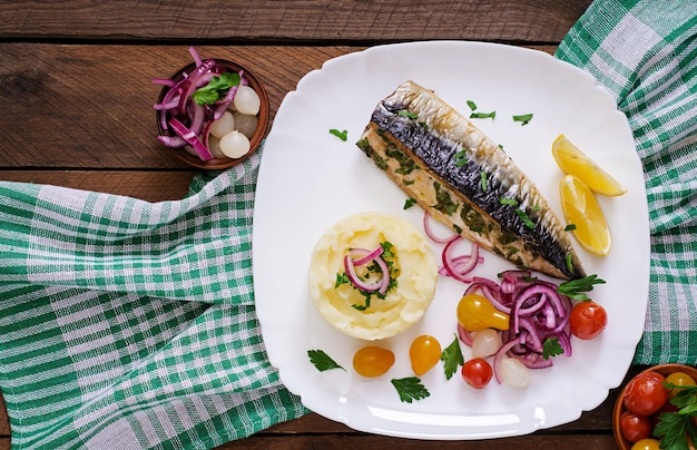 Gebackene makrele mit kräutern und garniert mit kartoffelpüree und eingelegtem gemüse. draufsicht