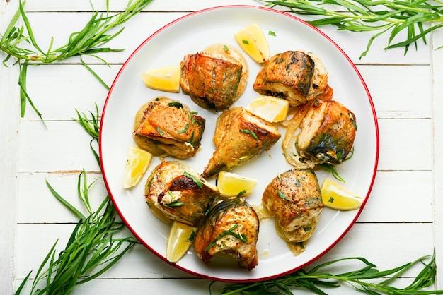 Gebackene makrele mit zwiebeln und kräutern. gebratene fischstücke auf einem teller. meeresfrüchte