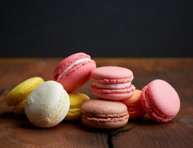 Gebackene mehrfarbige macarons kekse liegen in einer reihe auf einem braunen hölzernen hintergrund, nahaufnahme