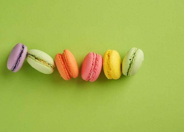 Gebackene mehrfarbige macarons-kekse liegen in einer reihe