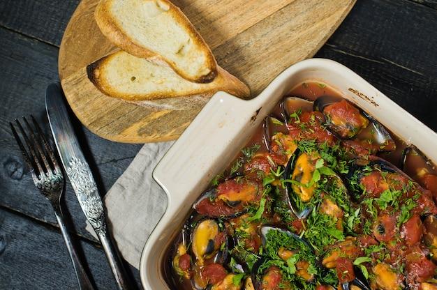 Gebackene miesmuscheln in tomatensauce mit koriander und parmesan.
