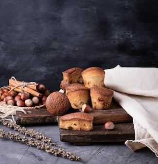Gebackene muffins mit trockenen früchten und rosinen auf einem braunen holzbrett, schwarzer tisch