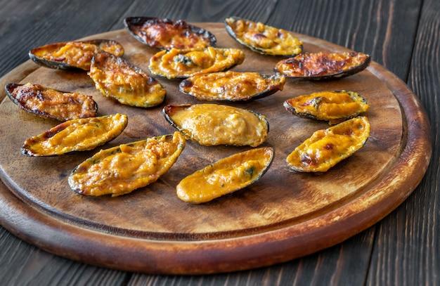 Gebackene muscheln gefüllt mit cheddar-käse-sauce