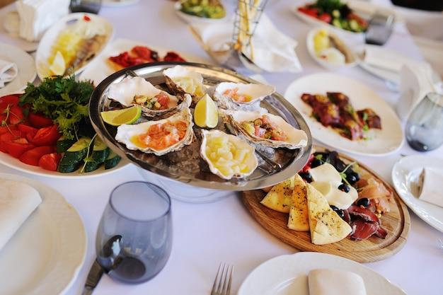 Gebackene muscheln mit käse, koriander und zitrone in austernschalen.