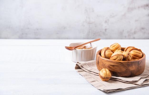 Gebackene nüsse mit karamell in einer holzschale auf einem weißen tisch. vorderansicht und kopierraum