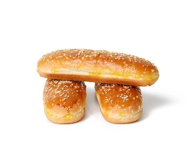 Gebackene ovale hot-dog-brötchen, backwaren mit sesam bestreut und isoliert auf weißem hintergrund, stapel