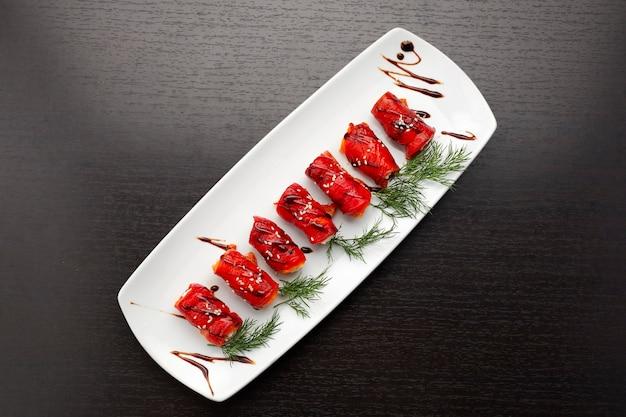 Gebackene paprika in brötchen mit frischkäse und dill, auf einem weißen teller, auf dunklem hintergrund