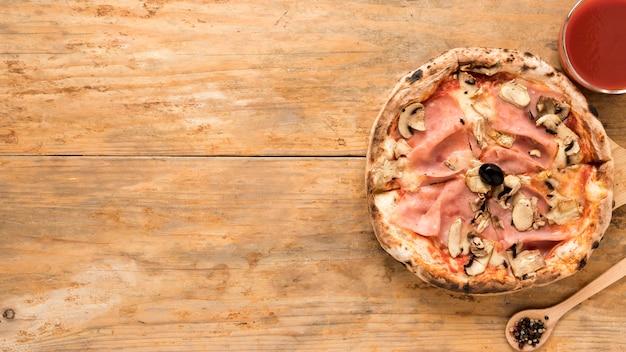Gebackene pilz- und speckpizza mit tomatensauce über altem holztisch