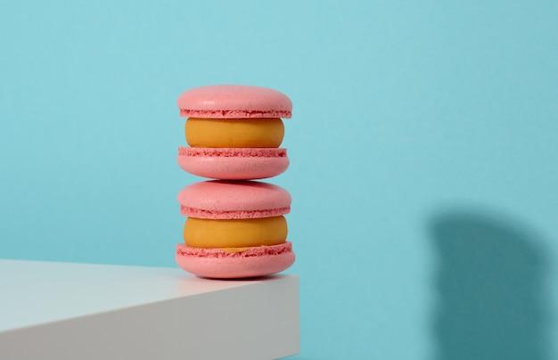 Gebackene pinke runde macarons auf blauem hintergrund, leckeres dessert