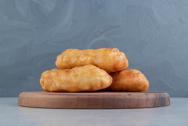 Gebackene piroshki mit kartoffeln auf holzbrett.