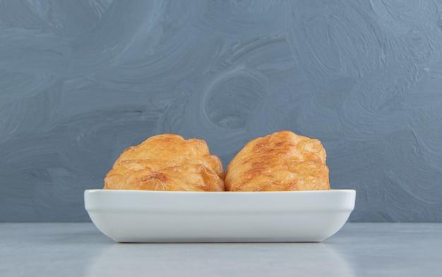 Gebackene piroshki mit kartoffeln in weißer schüssel.