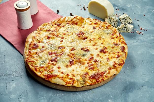 Gebackene pizza mit 4 käsesorten auf einem holzbrett