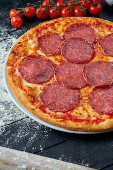 Gebackene pizza mit salami-chorizo mit roter sauce und geschmolzenem käse auf einem schwarzen holztisch in einer zusammensetzung mit zutaten. draufsicht