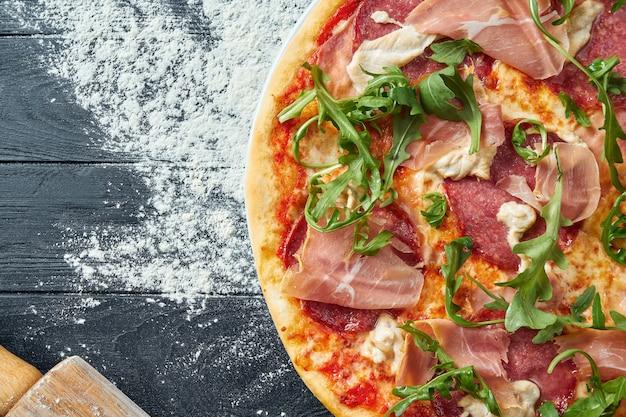 Gebackene pizza mit salami, schinken und hühnchen mit roter sauce und geschmolzenem käse auf einem schwarzen holztisch in einer komposition mit zutaten. draufsicht