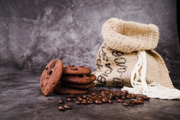 Gebackene plätzchen und röstkaffeebohnen mit sack auf rustikalem hintergrund
