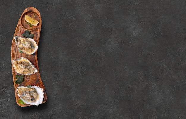 Gebackene rapana mit käse in schalen mit zitrone auf holzbrett auf grauer hintergrundoberansicht