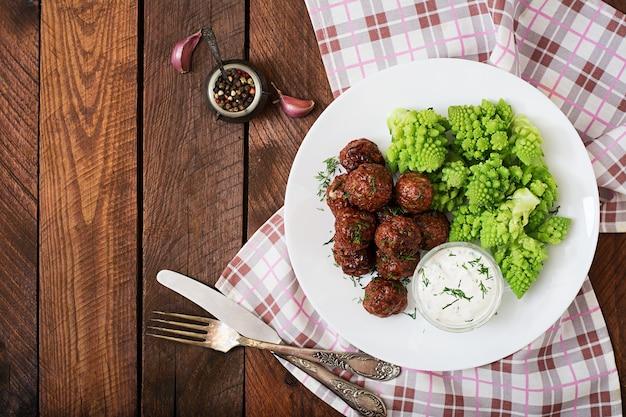 Gebackene rindfleisch frikadellen und garniert von gekochten kohl romanesko. diät-menü. richtige ernährung
