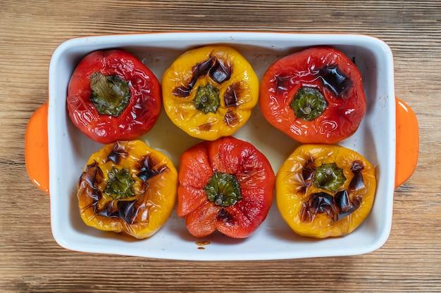 Gebackene rote und gelbe paprika. paprika in einer auflaufform auf einem holztisch. ein gesundes und leckeres vegetarisches gericht. nahaufnahme, ansicht von oben