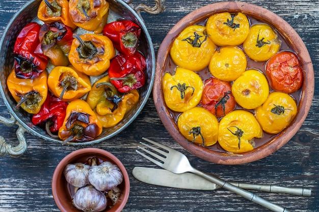 Gebackene rote und gelbe tomate und paprika. tomaten und paprika in einer auflaufform auf einem holztisch. ein gesundes und leckeres vegetarisches gericht. nahaufnahme, ansicht von oben