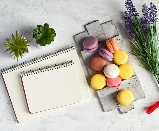 Gebackene runde mehrfarbige macarons auf einem hölzernen brett, stapel gewundene notizbücher