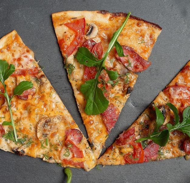 Gebackene runde pizza mit geräucherten würstchen, champignons, tomaten, käse und rucola