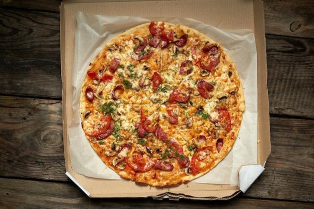 Gebackene runde pizza mit geräucherten würsten, pilzen, tomaten, käse und dill in einer offenen pappschachtel auf einem holztisch