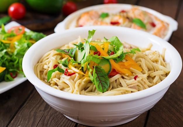 Gebackene scheiben roter und weißer fisch mit honig und limettensaft, serviert mit frischem salat und weichen nudeln in miso-brühe